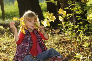 Kleines Maedchen spielt im Herbstwald