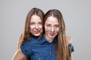 Studio portait of young and happy twin sisters embracing