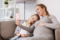 pregnant woman and girl taking smartphone selfie