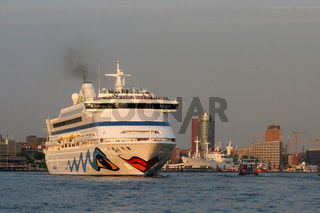 Das Kreuzfahrtschiff AIDAvita im Abendlicht beim Auslaufen aus dem Hamburger Hafen