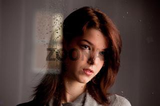 Nachdenkliche einsames junges Mädchen am Fenster