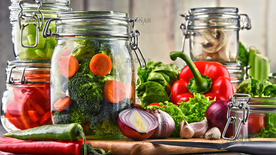 Jars with marinated food and raw vegetables on cutting board