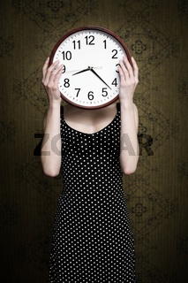 An image of a girl holding a big white clock