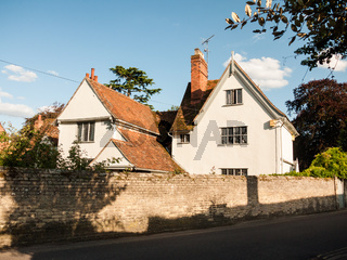 a white lovely cottage house in soft light and a brick wall and road in dedham