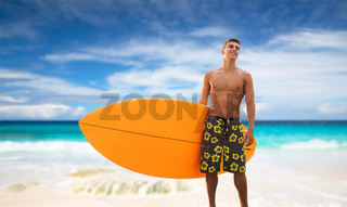 smiling young man with surfboard on beach