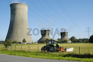 Farmer with tractor in front of the cooling towers of a power station