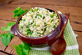 Couscous with spinach in bowl on board