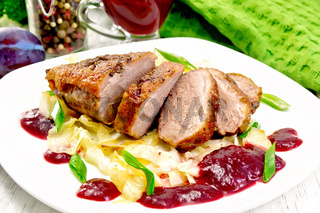 Duck breast with plum sauce and cabbage in plate on board