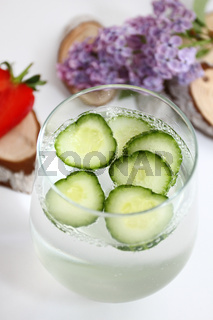 Detox flavored water with cucumber on white background with lilac and wood decoration. Healthy food