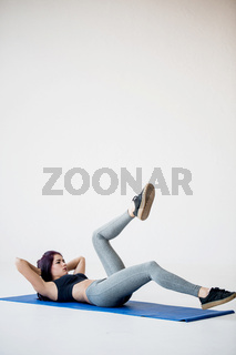 Sportive young brunette is doing the bicycle crunches while lying on the yoga mat in the white studio.