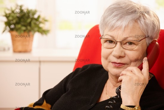 Senior woman with landline phone in hand