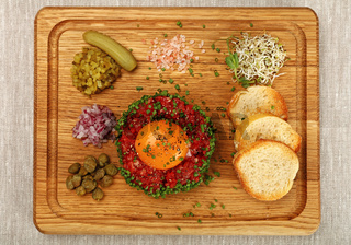 Raw meat tartare steak with egg yolk on wood board