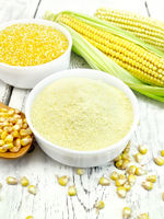 Flour and grits corn in bowls with cobs on board