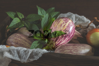 Purple graffiti eggplants, onion and green fresh basil in a wooden box in a vintage wooden background in rustic style, selective focus