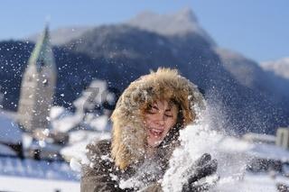 Junge Frau spielt in Bad Reichenhall mit Schnee