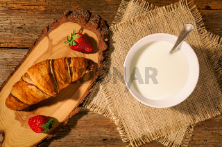 Continental breakfast with croissant, strawberries and a cup of milk