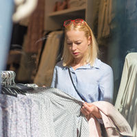 Beautiful woman shopping fashionable clothes in clothing store.