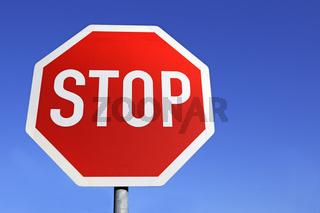 Stop Schild vor blauem Himmel