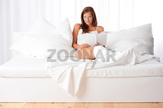 White lounge - Young woman sitting on white bed