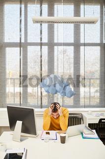 Manager mit Burnout und dunkler Wolke im Büro