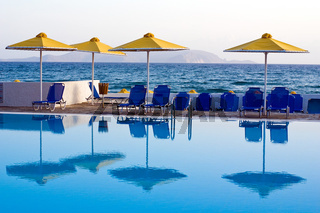 Reflection of umbrellas and lounges in the swimming pool on background seascape