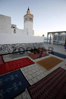 Teppiche und eine Moschee von einer Dachterasse in der Medina oder  Altstadt der Tunesischen Hauptstadt Tunis.
