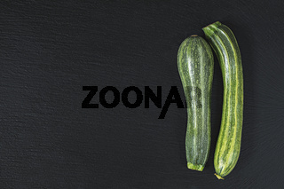 Two striped fresh green zucchini on a black stone surface.  Top view, copy space. Healthy eating concept.