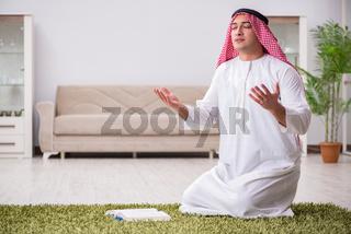 Arab man praying at home