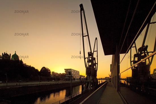 crane mirroring in Haus am Pegel at sunset, Neuss, Lower Rhine, North Rhine-Westphalia, Germany