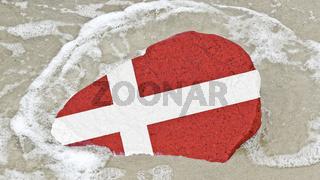 Flagge von Daenemark auf einem Findling am Ostseestrand