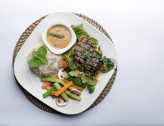 Beef filet steak served with rice, vegetables, and mushroom