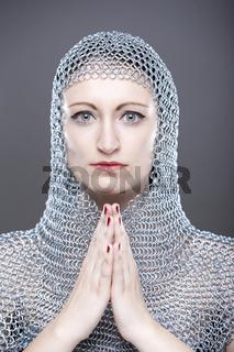 Junge Frau mit mittelalterlicher Kettenhaube und gefalteten Händen