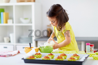 little girl baking muffins at home