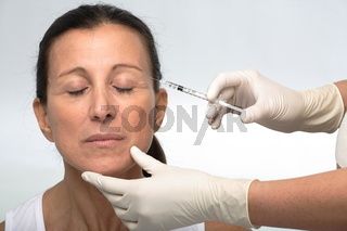 Mature attractive woman and a syringe of botox