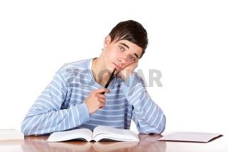Junger student sitzt müde und gelangweilt vor Büchern