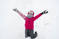 Girl playing with snow in winter