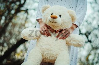Soft toy bear on hands of girl on sleepwear outdoor.
