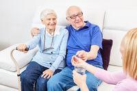 Pflegedienst Frau gibt einem Senior eine Tablette