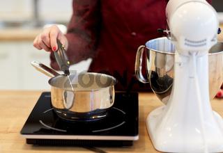 chef measuring temperature in pot at kitchen