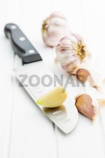 peeled garlic on knife