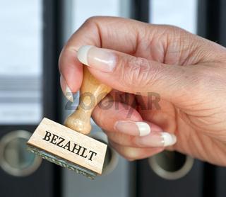 Bezahlt - Stempel mit Hand im Büro