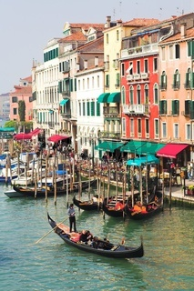 VENICE - APRIL 13: Gondoliers wait tourists on Grand channel
