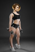 Attractive strong woman exercise with dumbbells