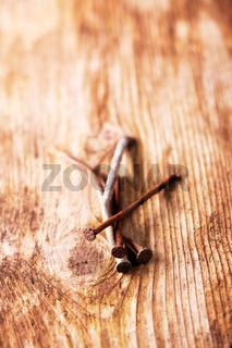 Nahaufnahme von rostigen Nägeln auf einem Holzbrett