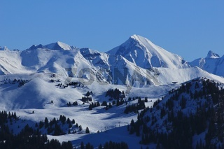 View of the Saanersloch ski slopes and snow covered mountains