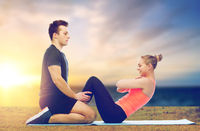 happy sportive couple doing sit-ups outdoor