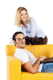 Happy couple on sofa with laptop computer