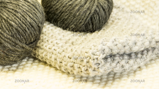 Knit piece with wool in a ball in gray and anthracite on a knickter Untergrund