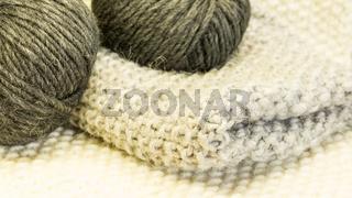 Strickstück mit Wolle im Knäuel in Grau und Anthrazit auf getricktem Untergrund