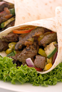 Fajita in tortilla with salad and vegetable as closeup on a white plate